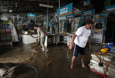 Workers of a hardware store start to clean up after being affected by flooded waters in Bundaberg, Queensland, Australia Jan. 1, 2011.  REUTERS/Daniel Munoz