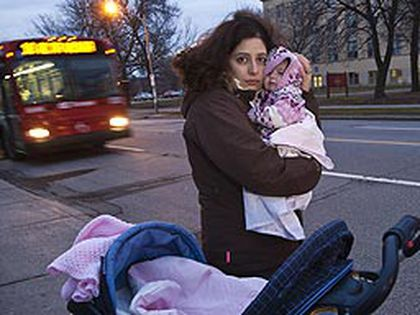 Nelly Elayoubi holds her newborn daughter Ayah as an OC Transpo bus goes by on Main Street in Ottawa, Dec. 3,2010. (ERROL MCGIHON/QMI Agency)