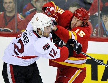 Calgary Flames' Tim Jackman (R) and Ottawa Senators' Mike Fisher collide during the second period of their NHL hockey game in Calgary, Alberta, February 9, 2011. REUTERS/Todd Korol (CANADA - Tags: SPORT ICE HOCKEY)