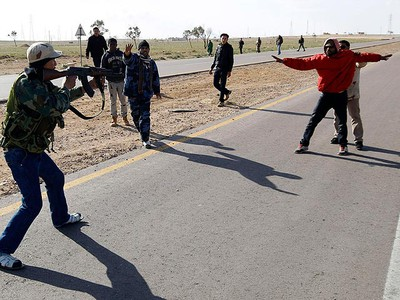 A rebel fighter points his gun at a suspected Gadhafi supporter as other rebels try to protect the suspected supporter, on a road between Benghazi and Ajdabiyah, near Ajdabiyah March 21, 2011. (REUTERS/Goran Tomasevic)