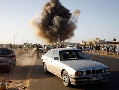 """A rebel fighter drives a car during an air strike in Ras Lanuf March 7, 2011. Libya's army fought rebels for control of Ras Lanuf on Monday and a rebel official said Moammar Gadhafi could attack oilfields like a """"wounded wolf"""" if the West did not stop him with air strikes.   REUTERS/Goran Tomasevic"""