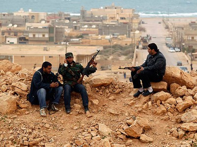 Rebel fighters sit at their position in Bin Jawad March 5, 2011. In the small town of Bin Jawad, where rebel forces were massing about 160 km from Sirte, they fired off rounds at warplanes and helicopters that had followed progress of the convoy to the coastal town and swooped over them.     (REUTERS/Goran Tomasevic)