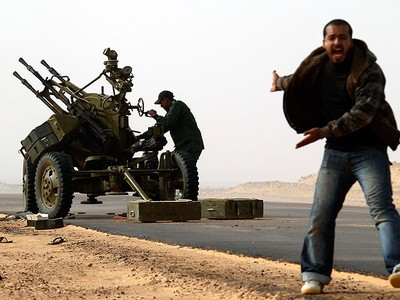 """A rebel fighter shouts during a battle near Ras Lanuf, March 4, 2011. Heavily armed rebels clashed with forces loyal to Muammar Gadhafi on Friday on the outskirts of the key oil terminal of Ras Lanuf as the head of Libya's rebel council vowed """"victory or death"""". The rebels were attacking a military base on the outskirts of Ras Lanuf, a major oil port on the Mediterranean Sea, which has a refinery, pipelines and a terminal, and the army responded with artillery fire and helicopters firing machine guns.   (REUTERS/Goran Tomasevic)"""