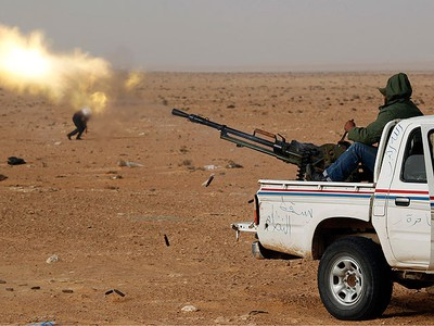 """A rebel fighter fires an anti-aircraft gun during a battle near Ras Lanuf, March 4, 2011.   Heavily armed rebels clashed with forces loyal to Muammar Gadhafi on Friday on the outskirts of the key oil terminal of Ras Lanuf as the head of Libya's rebel council vowed """"victory or death"""". The rebels were attacking a military base on the outskirts of Ras Lanuf, a major oil port on the Mediterranean Sea, which has a refinery, pipelines and a terminal, and the army responded with artillery fire and helicopters firing machine guns.  (REUTERS/Goran Tomasevic)"""