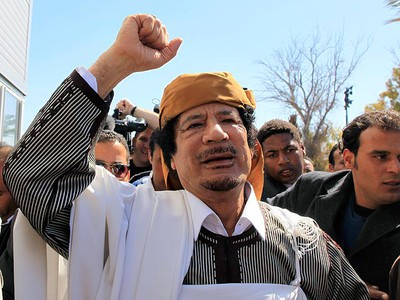 Libyan leader Muammar Gadhafi waves in Tripoli before making a speech which he sought to defuse tensions after more than 10 days of anti-government protests in Libya, March 2, 2011. Gadhafi, orchestrating a populist response to rebels threatening his rule, blamed al Qaeda on Wednesday for creating turmoil and told applauding supporters there was a conspiracy to control Libya and its oil.  (REUTERS/Ahmed Jadallah)