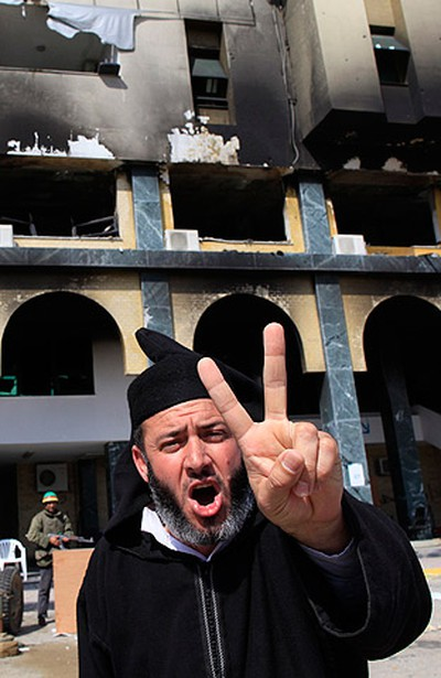 A protester opposed to Libya's leader Moammar Gadhafi gestures outside the burnt governor's office in the city of Zawiyah on February 27, 2011. (REUTERS/Ahmed Jadallah)