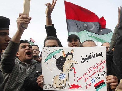 Protesters chant anti-government slogans while holding a poster depicting the Libyan leader Gaddafi in Benghazi city, Libya, February 23, 2011.  REUTERS/Asmaa Waguih