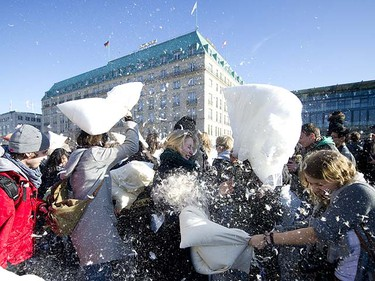 "People participating in a mass pillow fight ""flashmob"" event throw pillows at each other in front of the Brandenburger Gate in Berlin on March 20, 2011. AFP PHOTO / JOHANNES EISELE"