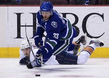 Vancouver Canucks' Henrik Sedin (33) is taken down by Edmonton Oilers' Jordan Eberle during the first period of their NHL hockey game in Vancouver, British Columbia April 2, 2011. (REUTERS/Ben Nelms)