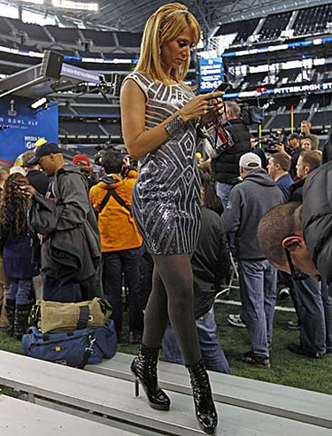 Mexican television reporter Ines Sainz texts from her phone as Pittsburgh Steelers quarterback Ben Roethlisberger is interviewed in the background during media day for Super Bowl XLV at Cowboys Stadium in Arlington, Texas, on Tuesday, Feb. 1, 2011. (REUTERS/Jeff Haynes)
