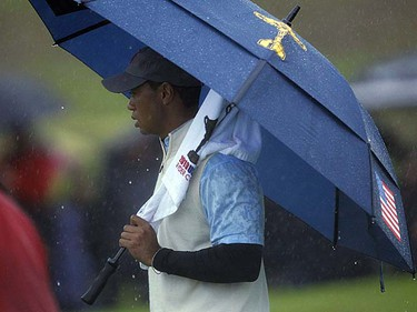 U.S. Ryder Cup team player Tiger Woods shelters himself under an umbrella on the first hole during four-ball play on the first day of the Ryder Cup at Celtic Manor in Newport, Wales on Friday, Oct. 1, 2010. (REUTERS/Brian Snyder)