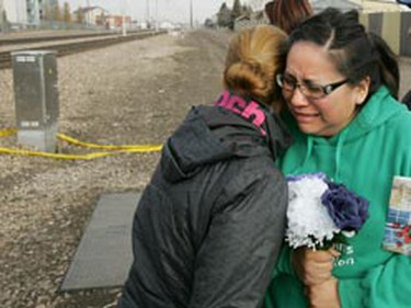 Janice Randhile cries as she arrives at the scene where her sister Delia Papastesis was struck and killed by an LRT train Tuesday night. (TOM BRAID/EDMONTON SUN)