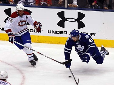 Nikolai Kulemin in the air as Hal Gill attempts to gain control of the puck. (CRAIG ROBERTSON, Toronto Sun)