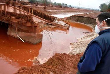 A resident stands next to a destroyed bridge in the flooded village of Kolontar, 150 km (93 miles) west of Budapest, October 5, 2010. Hungary declared a state of emergency in three western counties on Tuesday, the day after a torrent of toxic red sludge from an alumina plant reservoir tore through local villages, killing four people and injuring 120. Click here for the full story REUTERS/Bernadett Szabo