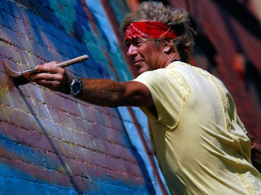 Artist Pierre Melancon paints a mural outside Herb and Spice on Bank St. Wednesday, September 1, 2010. Warm temperatures are expected through Friday with a cooling off for the weekend.  (Darren Brown/Ottawa Sun)