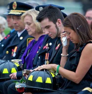Mourners Pamela Alspach (R), the daughter of Captain Patrick Glendinning of the Surrey Fire Service, and her brother Sam Glendinning (2nd R), attend the Canadian Fallen Firefighters Memorial Ceremony at Parliament Hill in Ottawa September 12, 2010. September 12,2010 (Errol McGihon/The Ottawa Sun)