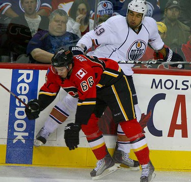 Calgary Flames T.J. Brodie (66) collides with Theo Peckham (49) in action during first period action between the Edmonton Oilers and the Calgary Flames in Calgary October 3, 2010. (Jim Wells/ QMI Agency)