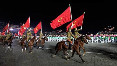 North Korean soldiers ride horses while carrying flags of the Workers' Party of Korea during a gala evening to commemorate the 65th anniversary of founding of the party in Pyongyang on Oct. 10, 2010. (REUTERS)