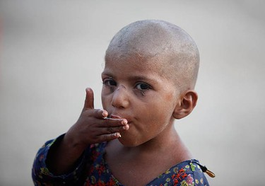 Fozia, 5, licks her fingers as she eats her meal while taking refuge in a makeshift relief camp in Sukkur in Pakistan's Sindh province August 20, 2010. Pakistan said it will clamp down on charities linked to Islamist militants trying to exploit anger among flood victims.  (REUTERS)