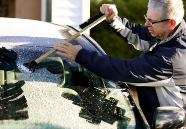 Mark Hardman scrapes the frost off of  his car's front windshield as he gets ready to take his son to school in west Edmonton on Friday September 17, 2010. This is the first heavy frost of the season. (TOM BRAID/EDMONTON SUN)