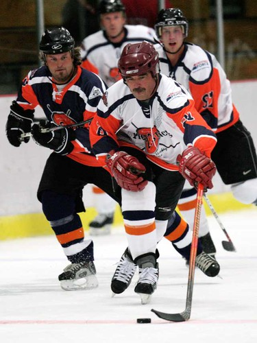 Former NHL player Kevin Primeau (in white) is chased by Ross Perkins (left in blue) as the two take part in The Pics and Sticks charity hockey game.  (DAVID BLOOM/EDMONTON SUN  QMI AGENCY)