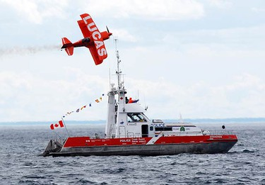 Mike Wiskus flies his stunt plane past a Canadian Coast Guard boat during the Canadian International Air Show at the Canadian National Exhibition in Toronto on Sept. 5, 2010. (CRAIG ROBERTSON, Toronto Sun)