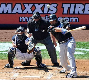 Toronto Blue Jays batter Vernon Wells hits a two-run home run in front of New York Yankees catcher Jorge Posada (L) and home plate umpire Fieldin Culbreth (C) in the first inning of their MLB American League baseball game at Yankee Stadium in New York, Sept. 5, 2010. (REUTERS)
