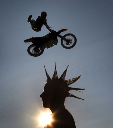 Aug 18/2010  Billy Von Vugt from Free Style Motocross performs air stunts Wednesday night with exhibition worker Chad Boucher watching at Lansdowne Park in Ottawa. The exhibition starts Thursday in Ottawa. Tony Caldwell/Ottawa Sun