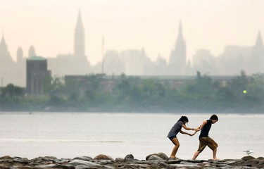 A heavy afternoon downpour didn't damper a little romantic interlude on the Ottawa River Tuesday, August 03, 2010, as Andrew Willman and Kristin Lagman venture out onto the rocks at Bate Island. (DARREN BROWN/QMI Agency)
