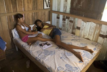 """Fourteen-year-old Elisany Silva, who measures 2.06 meters (6'9"""") tall, talks with her sister Talicia, 12, at her house in Braganca in the Brazilian Amazon state of Para August 29, 2010. Elisany, one of the world's tallest teens who was forced to quit school because she became too big to ride the bus, now dreams of becoming a famous fashion model. Picture taken on August 29, 2010. REUTERS/Paulo Santos"""