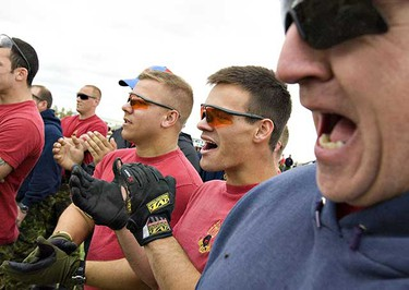 Spectators Master Warrant Officer Shaun Wright, right, Corporal Nathan Rommens, second right, and Corporal Nicholas Hryniw cheer during the 1 Combat Engineer Regiments' annual Logger Sports and Family Day at the Edmonton Garrison on Sunday, August 29, 2010, in Edmonton, Alberta. (AMBER BRACKEN/EDMONTON SUN)