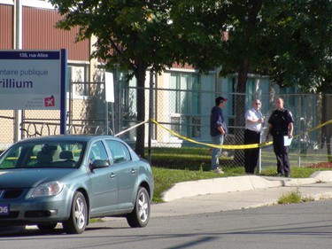Ottawa police investigate the discovery of a woman's body this morning at 120 Alice St. in Vanier. The victim was found in the parking lot beside the three-storey walkup.  (DARREN BROWN, Ottawa Sun)