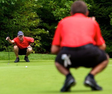 Randy Seymour (L) and his playing partner Stan Horton attempt to get a read on the green from both sides during play in the Ottawa Sun Scramble Open B Round #1 at the Le Sorcier Golf Course in Gatineau on Wednesday August 18,2010 (Errol McGihon/The Ottawa Sun)