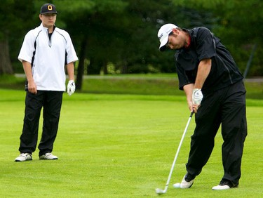 Dylan Villeneuve hits his approach shot as playing partner Ben McGovern watches during play on Championship Saturday of the Ottawa Sun Scramble at the Outaouais Golf Club in Rockland. August 21,2010 (Errol McGihon/The Ottawa Sun)