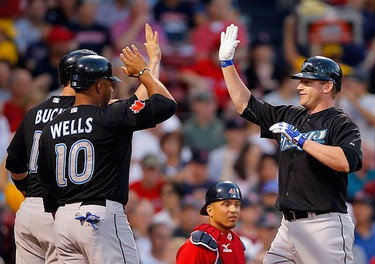 Toronto Blue Jays' Lyle Overbay (R) is congratulated by John Buck and Vernon Wells after hitting a three-run home run against the Boston Red Sox during the first inning of their MLB American League baseball game at Fenway Park in Boston, Massachusetts August 20, 2010.  (REUTERS)