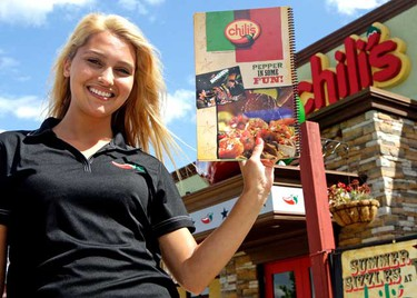 """Server Caitlin Giordmaina shows off the new """"Left Handed"""" menu at Chili's August 16th, 2010 in Toronto. The menu is bound on the right side and flips backwards from a right handed menu. (Dave Abel/QMI Agency)"""