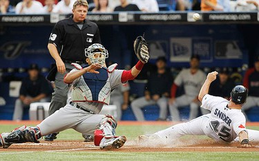 Toronto Blue Jays runner Travis Snider scores on a sacrifice fly past Boston Red Sox catcher Victor Martinez (L) during the first inning of their MLB American League baseball game in Toronto August 11, 2010. (REUTERS)