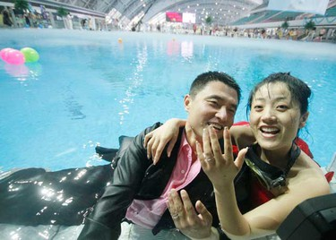 A happy couple celebrate their nuptials by tying the knot in a swimming pool in Nanjing, China. But the ceremony didn't come cheap - the pool cost 20,000 RMB ($2,950/£1,965) to rent alone, while the underwater camera, diving coach and site decoration were an extra 50,000 RMB ($7,380/£4,920). (WENN.com)