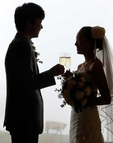 Japanese bridal couple Arisa Chi (R) and her new husband Kenji Yoshida toast after their wedding ceremony on the foggy Mount First (2168m/7113ft) in the Swiss Alpine resort of Grindelwald August 6, 2010. (REUTERS)