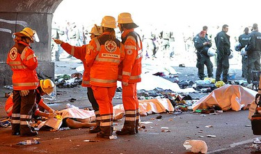 """Red Cross rescuers and German police officers stand next to the bodies of stampede victims in Duisburg July 24, 2010. At least 15 people were killed and some 80 people were injured in a stampede at the """"Love Parade"""" techno music festival in the western German city on Saturday, after overcrowding at an entrance gate sparked a stampede, police said. (REUTERS)"""