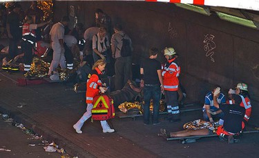 """People injured in the stampede at the Love Parade """"The art of Love"""", receive first aid in the western German city of Duisburg July 24, 2010. At least 15 people were killed and some 80 people were injured in a stampede at the """"Love Parade"""" techno music festival in the western German city on Saturday, after overcrowding at an entrance gate sparked a stampede, police said. (REUTERS)"""
