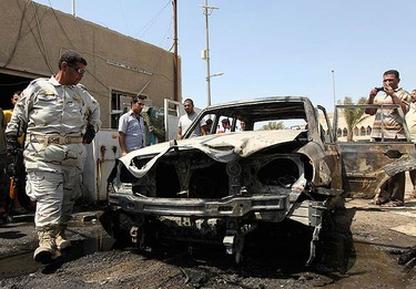 A policeman inspects a damaged vehicle after a bomb attack in Baghdad July 18, 2010. A bomb attached to a car killed one man and wounding three others in Ur district, northeastern Baghdad, police said.  (REUTERS)