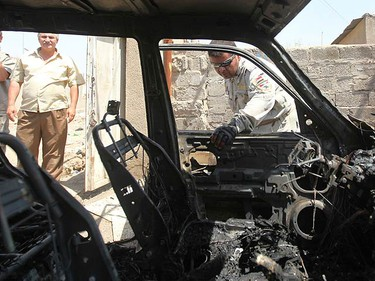 A policeman looks inside a damaged vehicle after a bomb attack in Baghdad July 18, 2010. A bomb attached to a car killed one man and wounding three others in Ur district, northeastern Baghdad, police said.  (REUTERS)