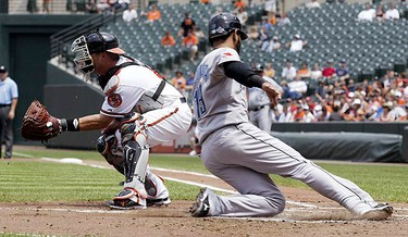Toronto Blue Jays base runner Jose Bautista (R) slides across home plate safely as Baltimore Orioles catcher Jake Fox awaits the late throw in the second inning of their MLB American League baseball game in Baltimore, Maryland July 18, 2010.  (REUTERS)