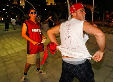 Miami Heat fan Felix Castillo (R) shows off a makeshift LeBron James teamshirt as he celebrates with Nik Nevins after the NBA star announced his free agency plans in Miami July 8, 2010. James announced he would be joining free agents Chris Bosh and Dwyane Wade and will sign with the Miami Heat after two months of deliberation and endless speculation.  (REUTERS)