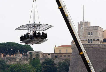 """Guests have dinner at an event known as """"Dinner in the Sky"""" as they are seated around a table lifted by a crane in the harbour of Monaco, July 9, 2010. (REUTERS)"""