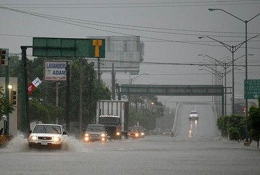Vehicles are driven along a flooded street caused by heavy rains from hurricane Alex in Matamoros, in the Mexican state of Tamaulipas June 30, 2010. Hurricane Alex strengthened into a Category 2 storm over the Gulf of Mexico on Wednesday and was due to hit northeastern Mexico very soon, the U.S. National Hurricane Center said. (REUTERS)