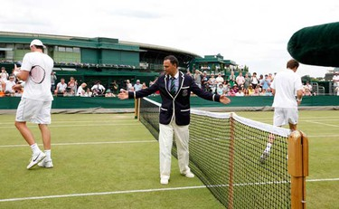 Umpire Mohamed Lahyani (C) stands on court 18 before the resumed match between France's Nicolas Mahut (R) and John Isner of the U.S. at the 2010 Wimbledon tennis championships in London, June 24, 2010.   (REUTERS)