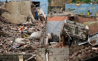 A boy is seen over his destroyed house after heavy rains in Uniao dos Palmares city, in the northeastern state of Alagoas June 23, 2010. Flood waters devastated towns and villages in northeastern Brazil, killing at least 42 people and leaving more than 600 missing, emergency officials said. (REUTERS)