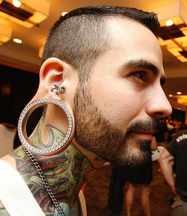 Efix of Quebec City shows off his tats and bling body modification spacer that is 10 years in the making. (JACK BOLAND, Toronto Sun)